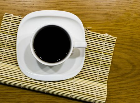 Hot Coffee in white coffee cup on Bamboo Mate , Photograph from top view Stock Photo