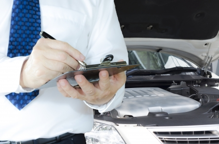 Technician writing on a clipboard standing in front of a car at work Stock Photo
