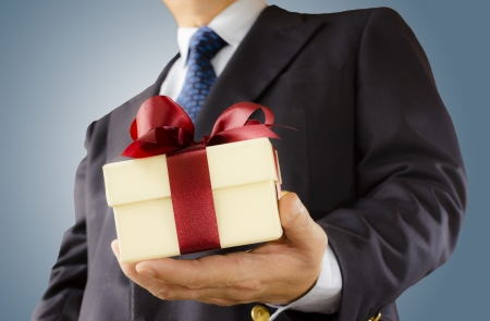 Businessman holds out the gift box ,isolated background