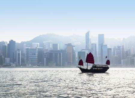 Dschunke im Hafen von Hongkong mit Stadtbild im Nebel im Hintergrund Standard-Bild - 18120537