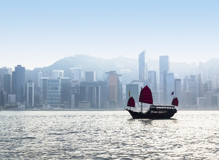 Junk Boat in Hong Kong harbor with cityscape under fog in background photo