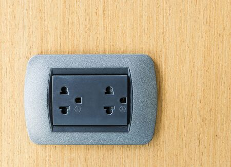 Electric wall plug on a wooden wall photo