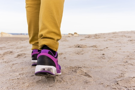 Woman with sneakers jogging on a beach photo