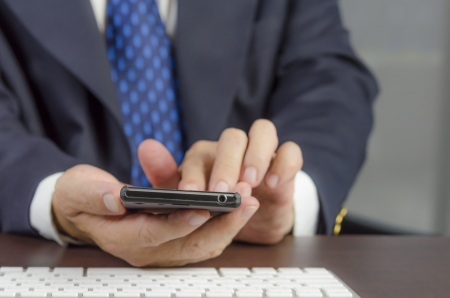 Businessman using mobile phone with touch screen,Focus on Phone photo