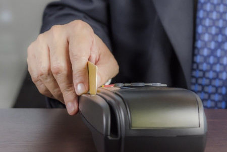 Close up of businessman hand using credit card machine