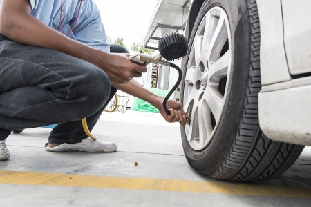 inflating: Man checking pressure and inflating car tire