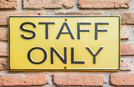 Staff only sign on brick wall photo
