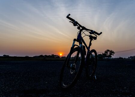 Beautiful close up scene of bicycle at sunset, silhouette of bike forward to sun Stock Photo