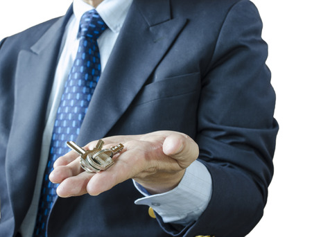 key: Businessman with house key in hand, isolated on white background