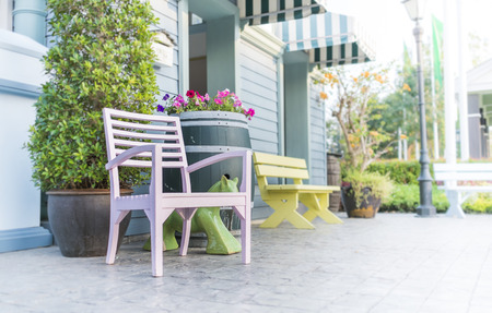 View of a large front porch with wood chairs photo