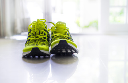 athletic wear: Green Sport running shoes on the floor