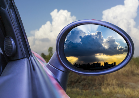 Rear view mirror reflecting cloudy sky Imagens