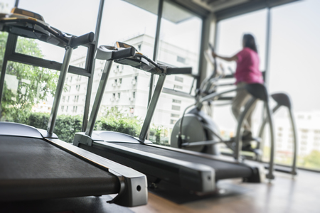 girl in sportswear: Blurred of woman exercising at the gym on a cross trainer Stock Photo