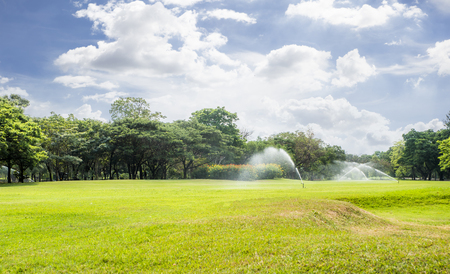 Watering the Lawn and park with Sprinkler in the morning Stock Photo