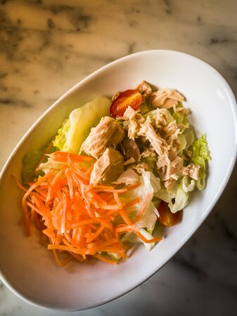 Top view of tuna salad with fresh vegetables on marble table