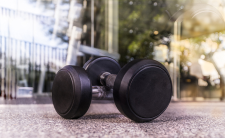 Dumbells on the floor in fitness room  in the morning : Concept for Healthy Stock Photo