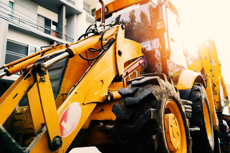 Close up of yellow construction vehicle parking in the construction site of town home building 스톡 콘텐츠