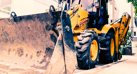 Close up of yellow construction vehicle parking in the construction site