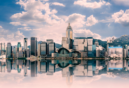Hong Kong cityscape in the morning : View from Victoria Harbour with beautiful sunrise and reflection