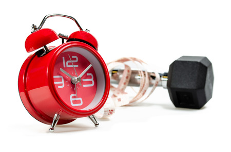 Alarm clock Measurement tape and dumbbell on white background : Concept for time to workout