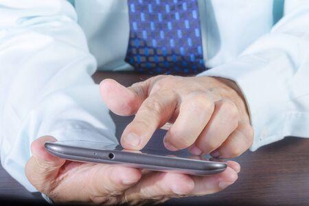Businessman hand holding and using digital tablet Standard-Bild - 130675483