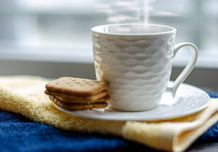 Hot coffee in the white mug and crackers setting for coffee break in the morning