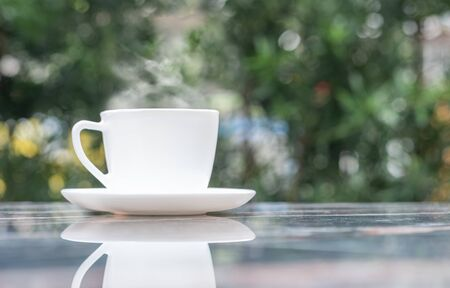A cup of hot coffee in white cup with steaming at garden in coffee shop Standard-Bild - 130672996