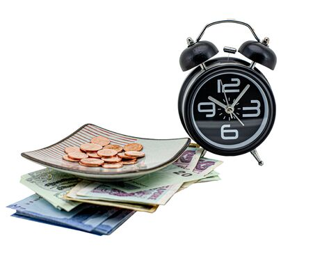 Alarm clock and banknote under coins in saucer , Isolated on white background Standard-Bild - 131976745