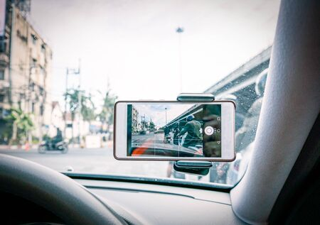 Driving car in the city with mobile phone recording video of traffic Standard-Bild - 131976861