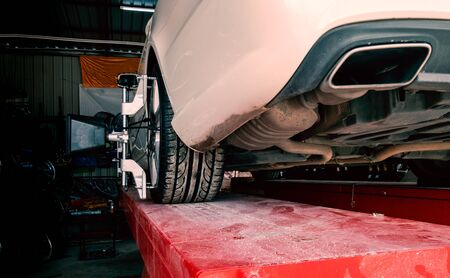 Tire clamped with lazer aligner undergoing auto wheel alignment in modern garage service Standard-Bild - 131976710