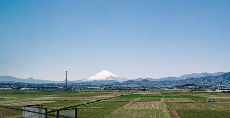 Japanese countryside with rice field and fuji mountain in background , View from high speed train