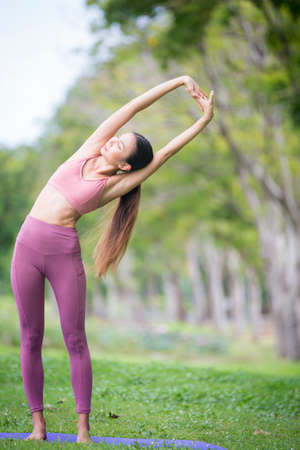 Asian model poses yoga in a park on a natural green background, health care concept, beautiful body structure, fit body