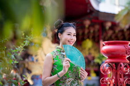 Action portrait beautiful Asian girl wearing Cheongsam green dress. the celebration of something in a joyful and exuberant way. Festivities and Celebration concept
