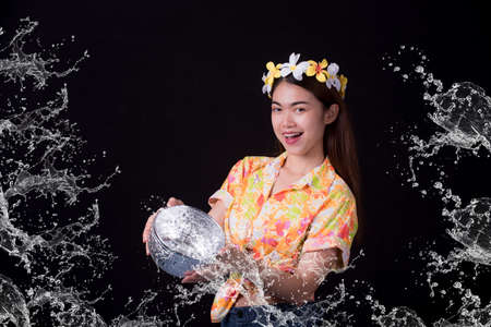 Thai girl smiling Asian beauty Swimming with ancient bowls Preserve the good culture of Thai people during Songkran festival. Thai New Year, Family Day in April