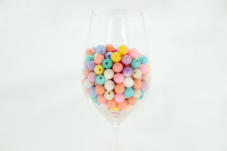 colorful beads: colorful beads on a glass of wine .