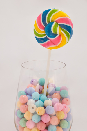 colorful beads: Lollipop colorful beads on a glass of wine . In light sweet warm tone