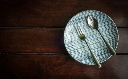plate setting: Dish plate with silver fork and spoon On old wooden table . Dinner place setting.