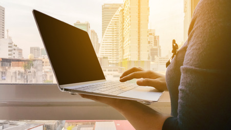 business woman Standing by the window with views of the city and Using laptop Then look at the Sun light .