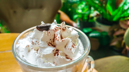 Coffee cappuccino with whip cream fluffy white milk on top. Placed on a wooden table ready to serve you.