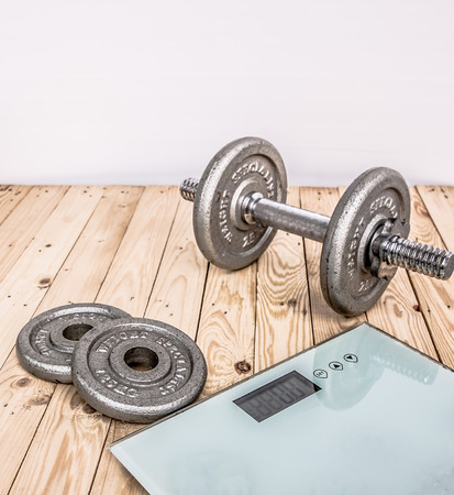 Dumbbells , weight plates and bottle of water on wooden background for bodybuilder. Concept for sport player or workout. gym of accessories for fitness