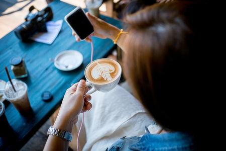 Happy business young woman taking selfie with Smart Phone Enjoyment with Cappuccino , Latte art coffee and relax In her holiday .