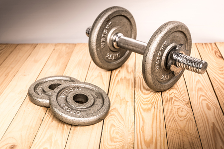 Dumbbells , weight plates on wooden background for bodybuilder. Concept for sport player or workout. gym of accessories for fitness Stock Photo