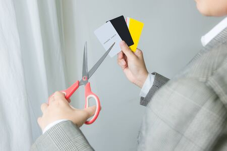 eliminate: businessman cutting up credit card with scissors over contract and other . Destroy for protection money