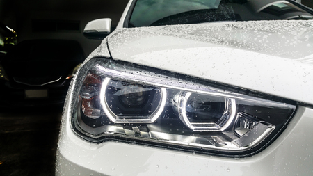 Modern car headlights Front of White car On the day of wet wipers. Garage Theme