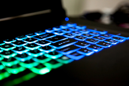 Closeup of enter on a keyboard illumination Multicolour Rainbow colors for play Games Online. backlit keyboard Concept
