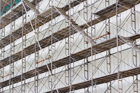 apartment shortage: scaffolding for construct a building under construction. Stock Photo