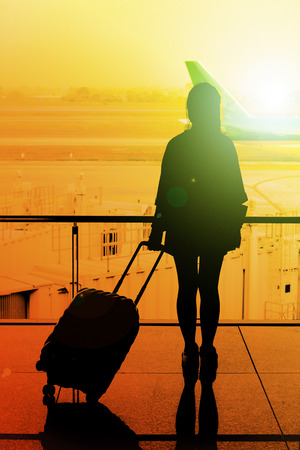 silhouette of young girl with luggage in the terminal at the airport.