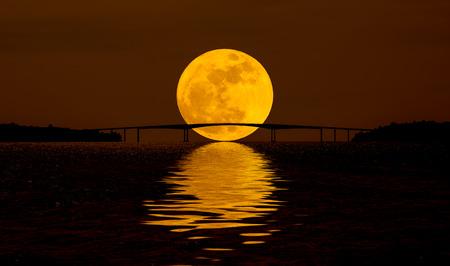 Full moon over night water behind the bridge