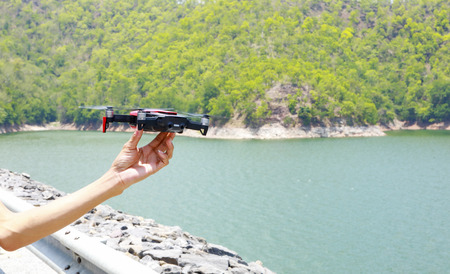 drone with the professional camera takes pictures of the reservoir in the mountains Imagens