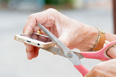 The old mans hand holding scissors and cut mobile phone. Reklamní fotografie